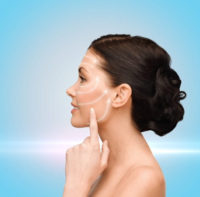 beauty, spa and health concept - smiling young woman pointing to her cheek