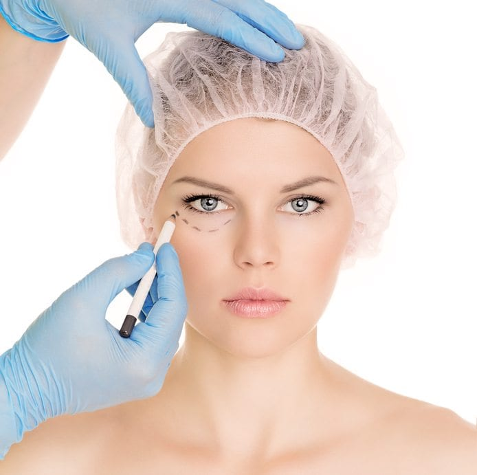 Plastic surgeon drawing lines over eyelid of a nice young female before cosmetic operation, isolated over white background.