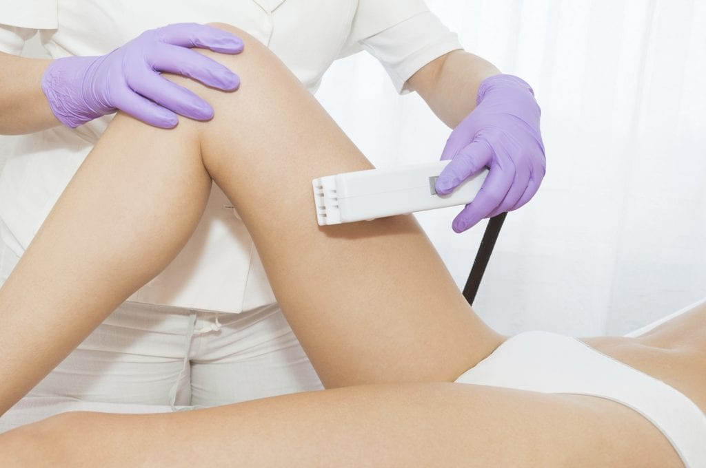 clinician removing leg hair using laser technology