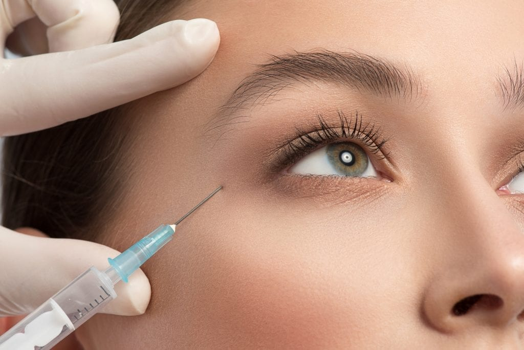 Close up of female eye area getting botox injection by syringe