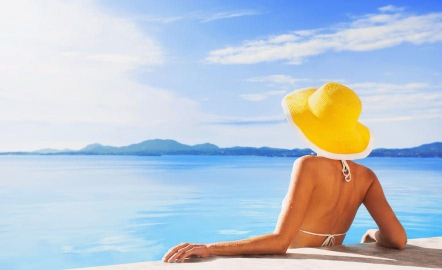 Woman wearing yellow sun hat enjoying the sun in a pool