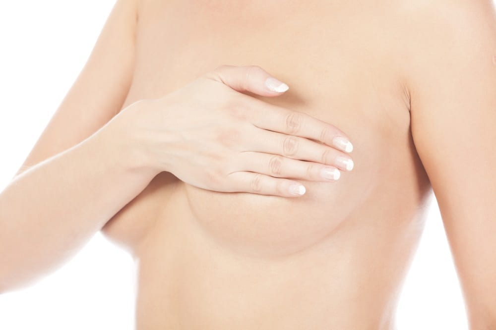 woman holding her breast, isolated on white background