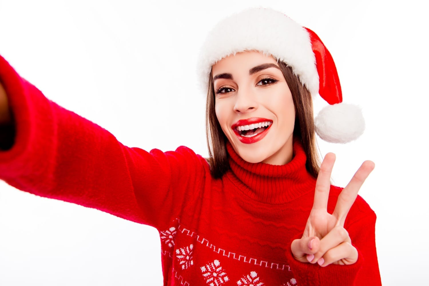 Cheerful woman in santa hat making selfie