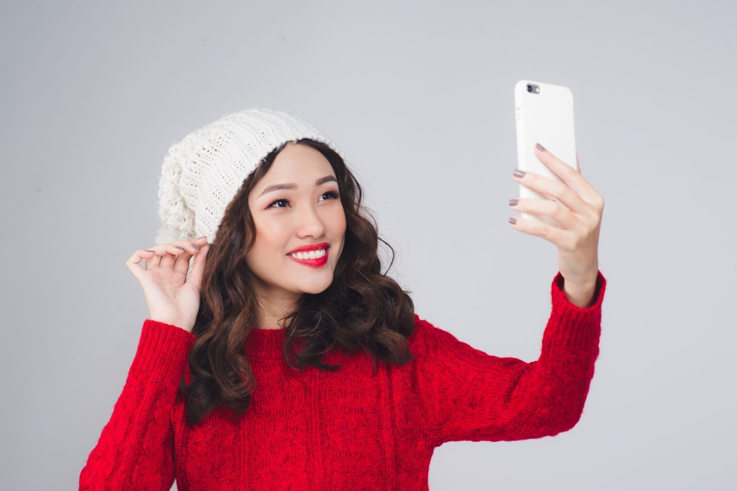 Happy young woman wearing winter clothing taking a selfie photo