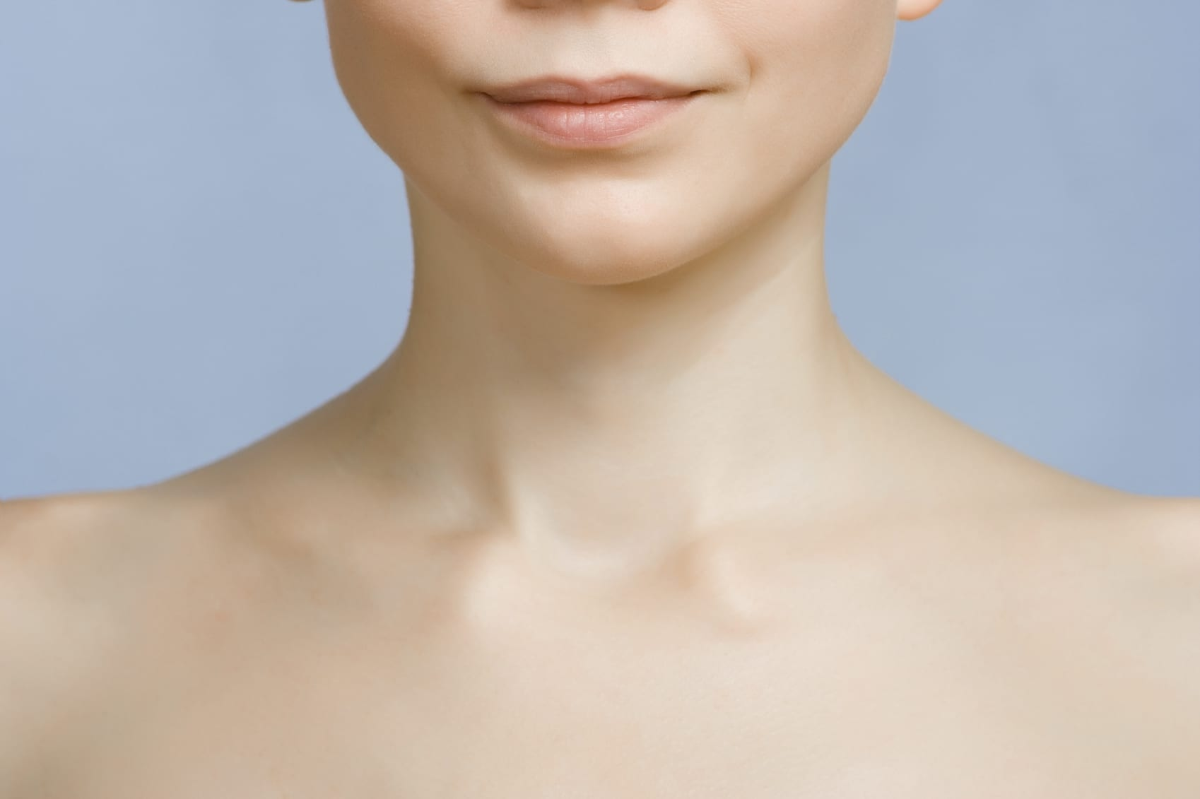 An image of young woman's lips, chin and shoulders. Focus is set at her lips and chin
