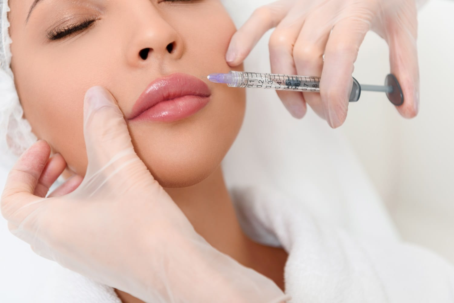 Close up of beautician hands in gloves injecting female lips with botox