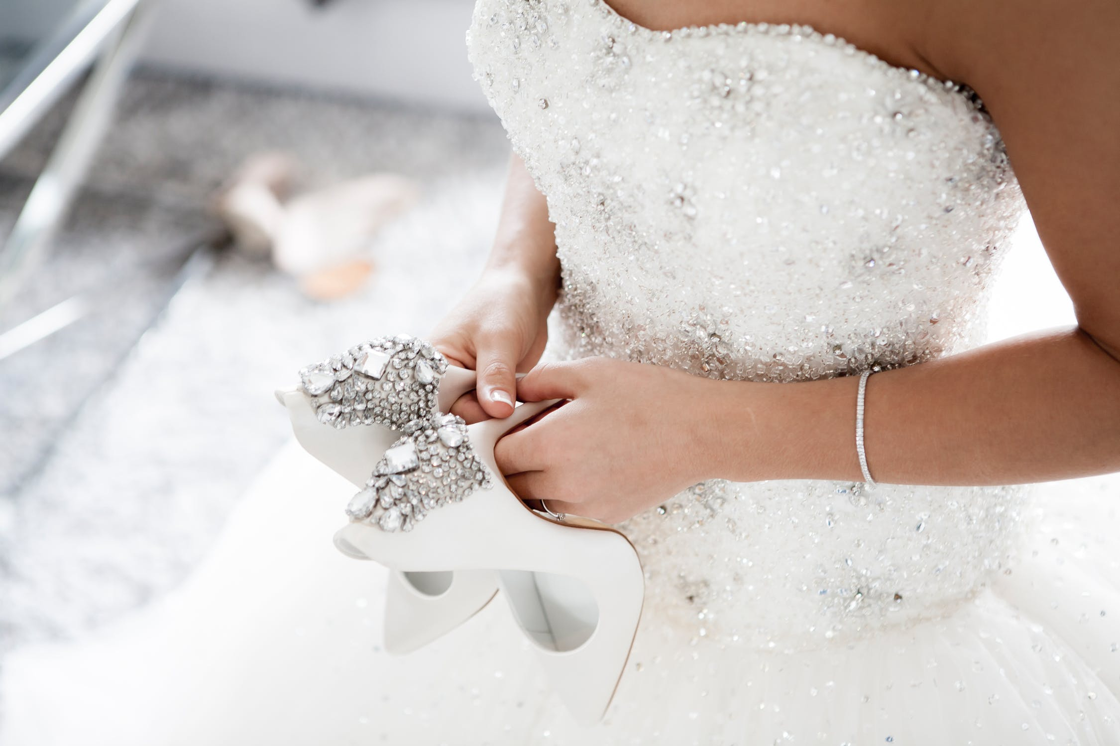 Bride holding her high heel shoes