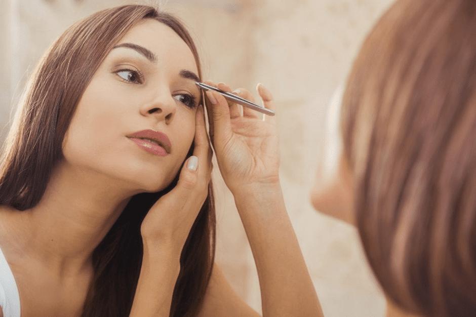 woman using tweezer on eye brow