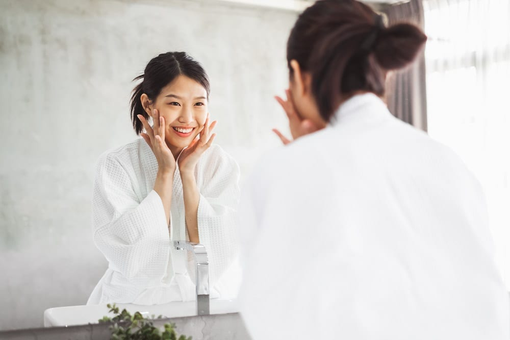 woman cleaning face front of mirror, skin care
