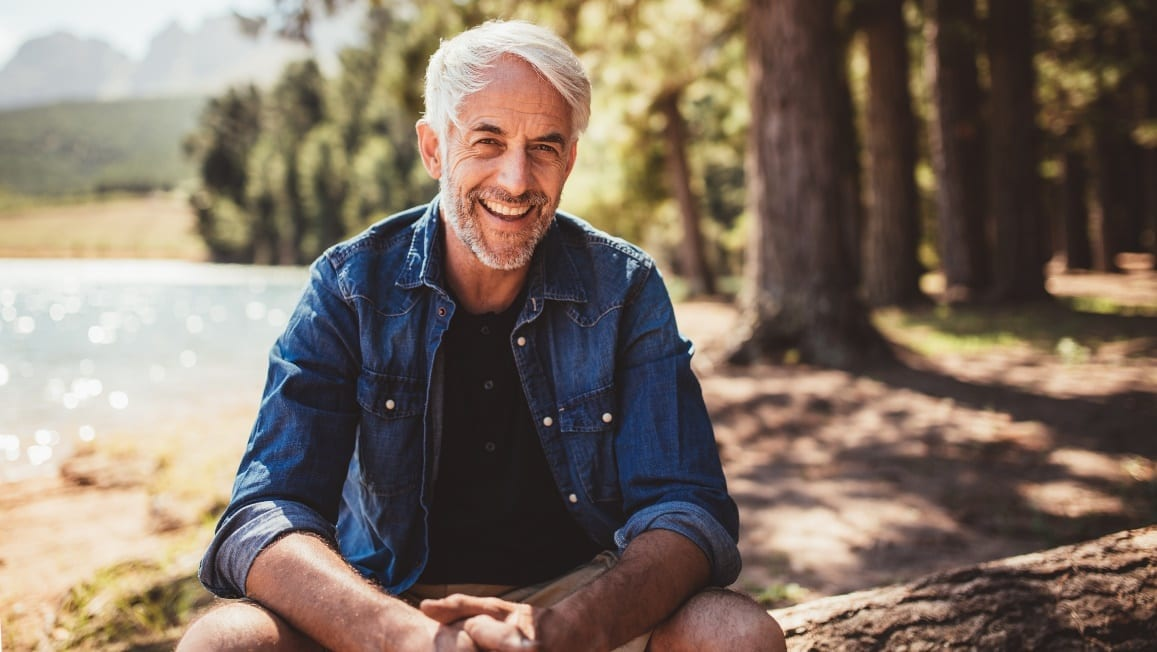 man sitting down on tree trunk smiling