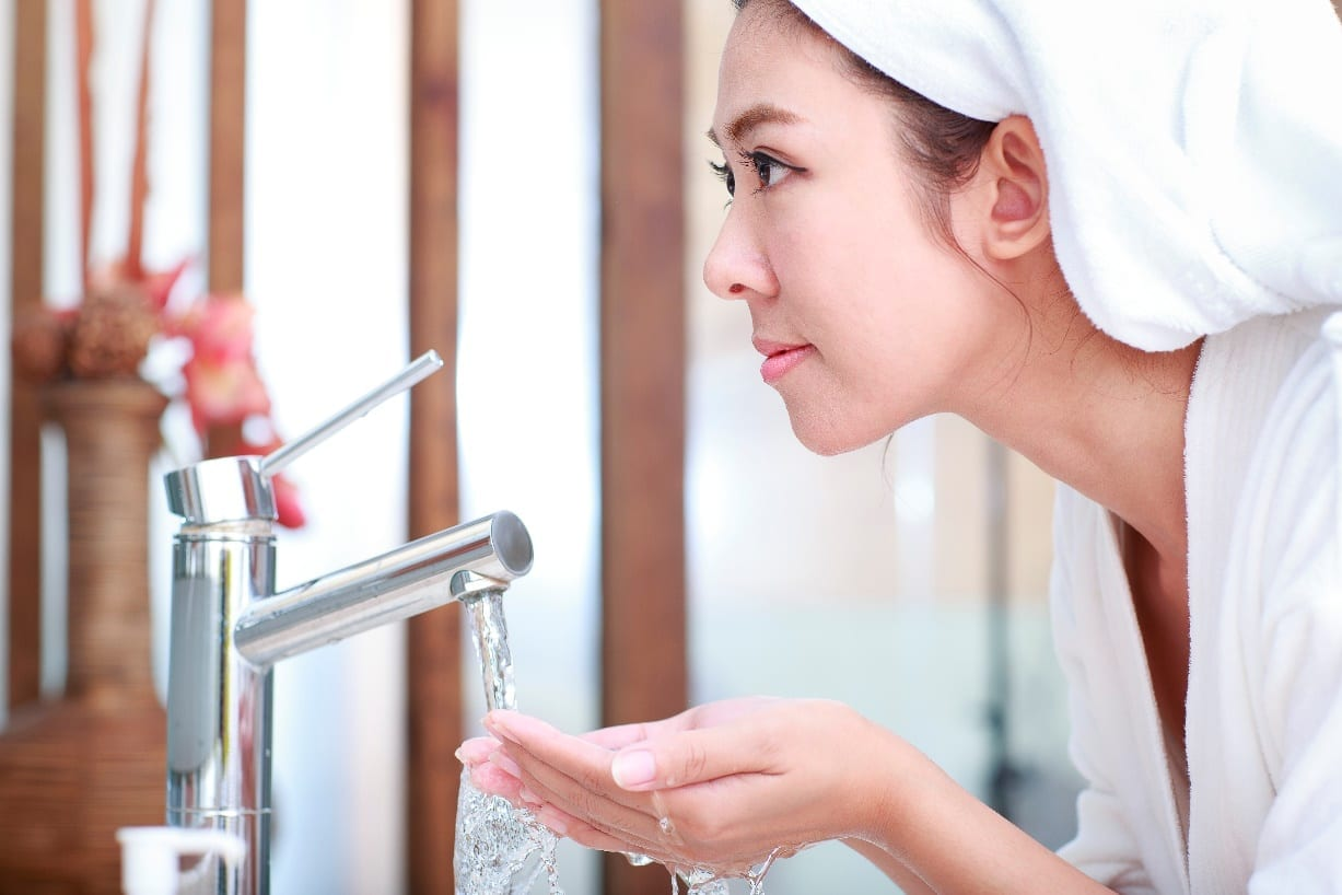 woman cleaning her face with water