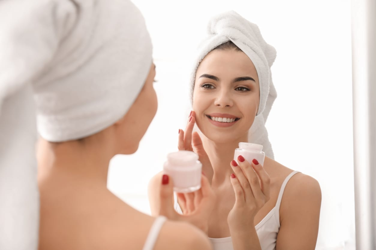 Morning of beautiful young woman applying facial cream in bathroom