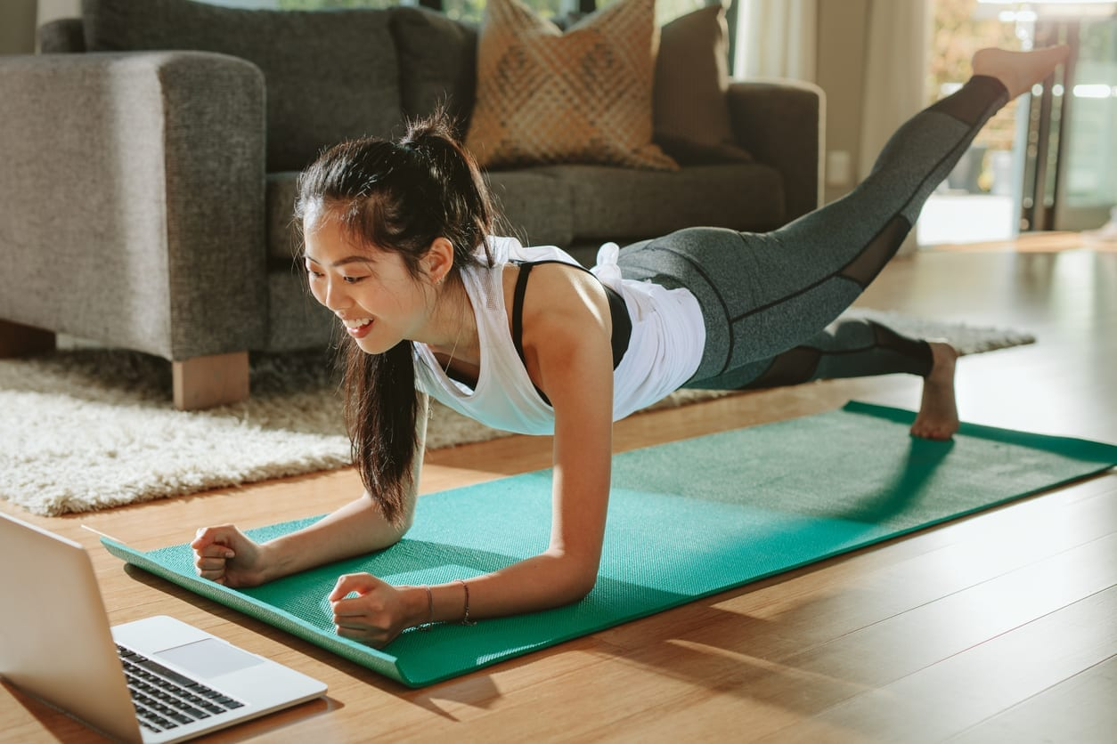 Smiling woman exercising at home and watching training videos on laptop. Chinese female doing planks with a leg outstretched and looking at laptop