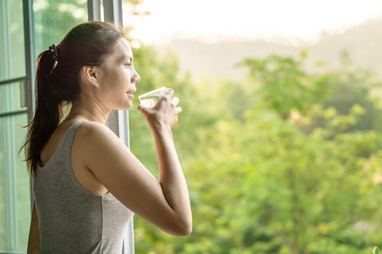 woman drinking clean water in the morning next to the window with nature