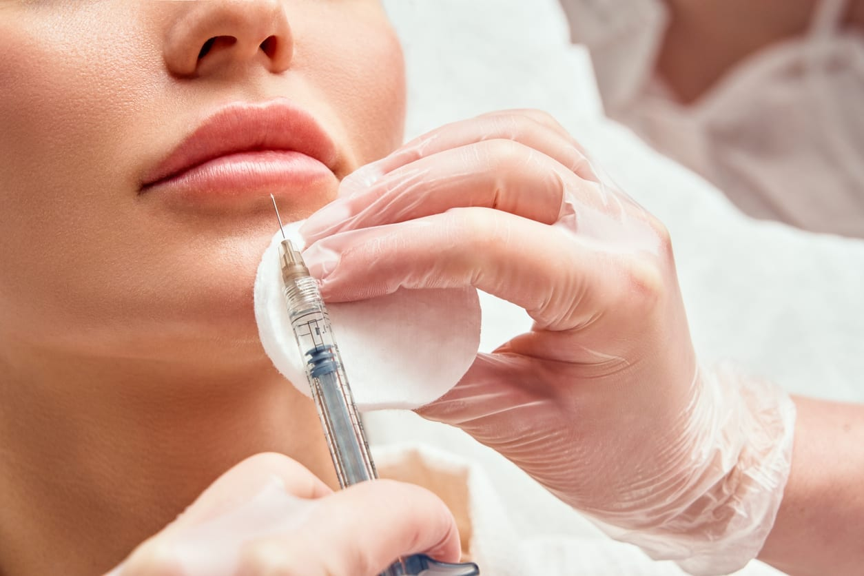 lip shape correction procedure in a cosmetology salon. The specialist makes an injection on the lips of the patient. Lip augmentation