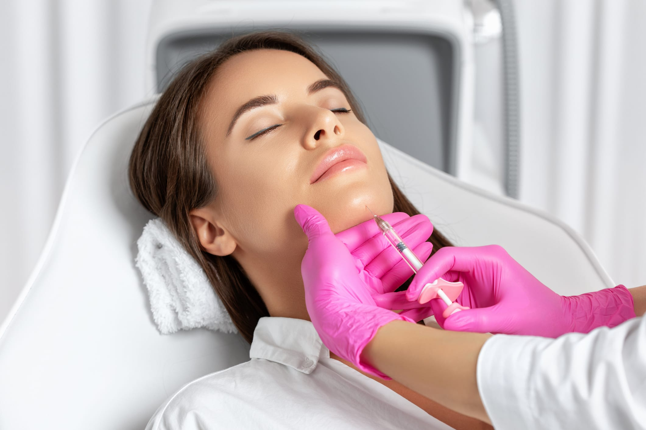 Woman having chin injected with filler