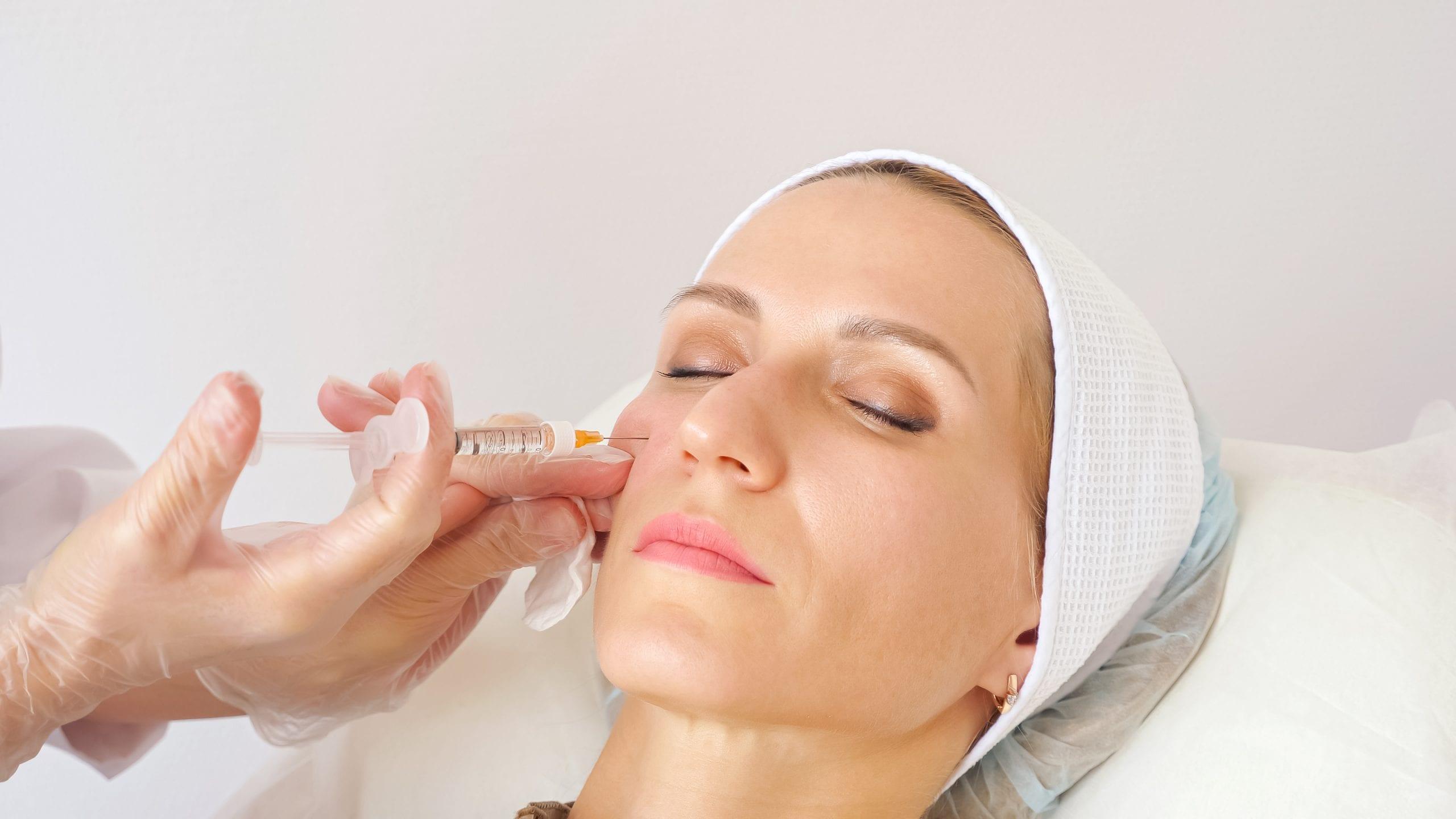 Beautician giving woman cheek injection