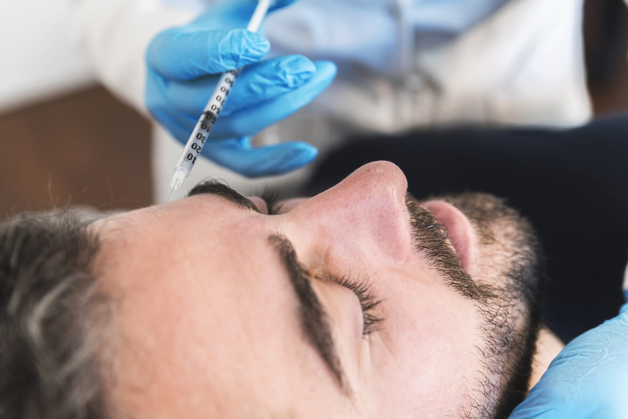 Close up of man at clinic receiving injection fillers on forehead.