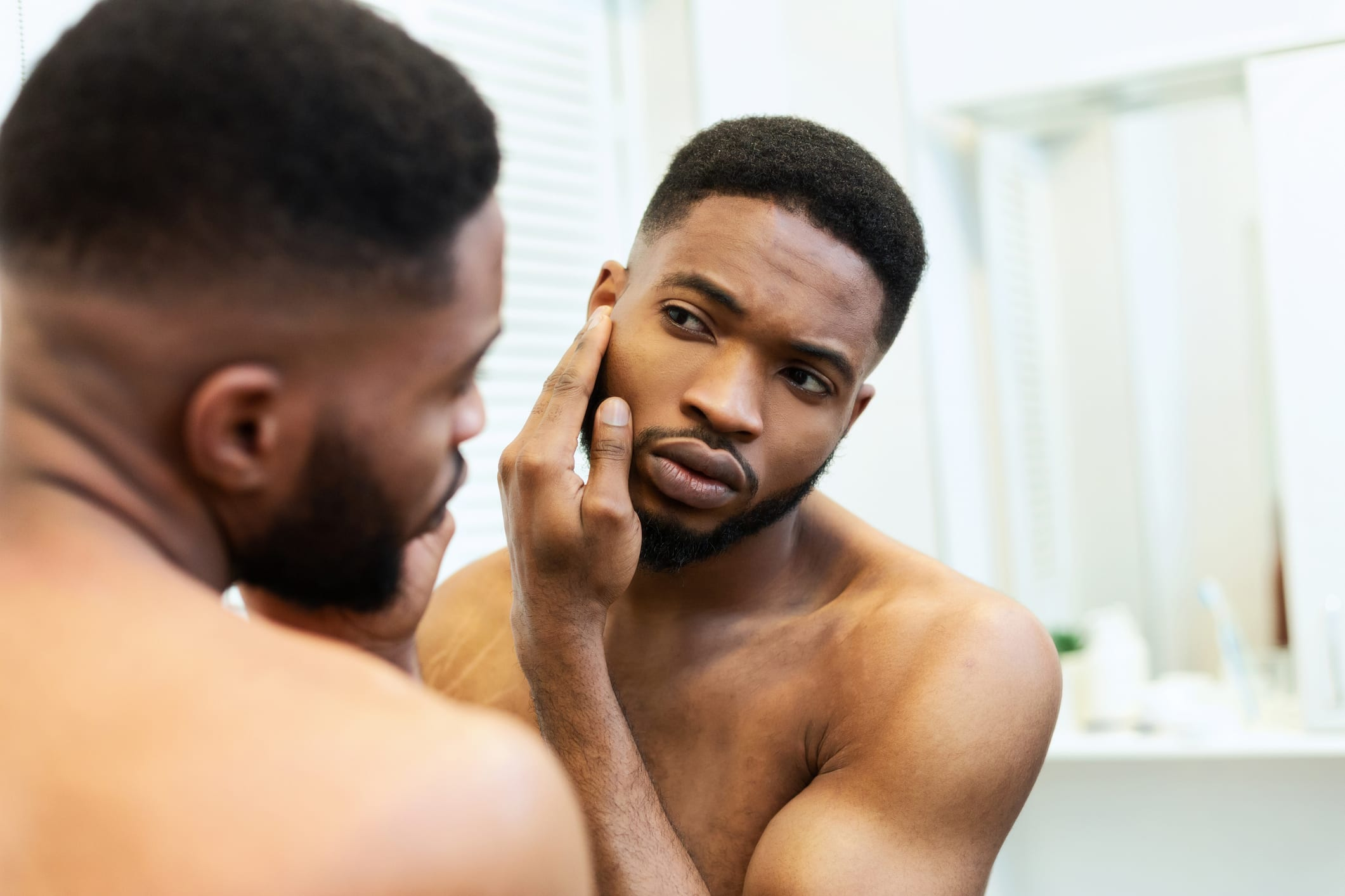 Young guy checking his face in mirror