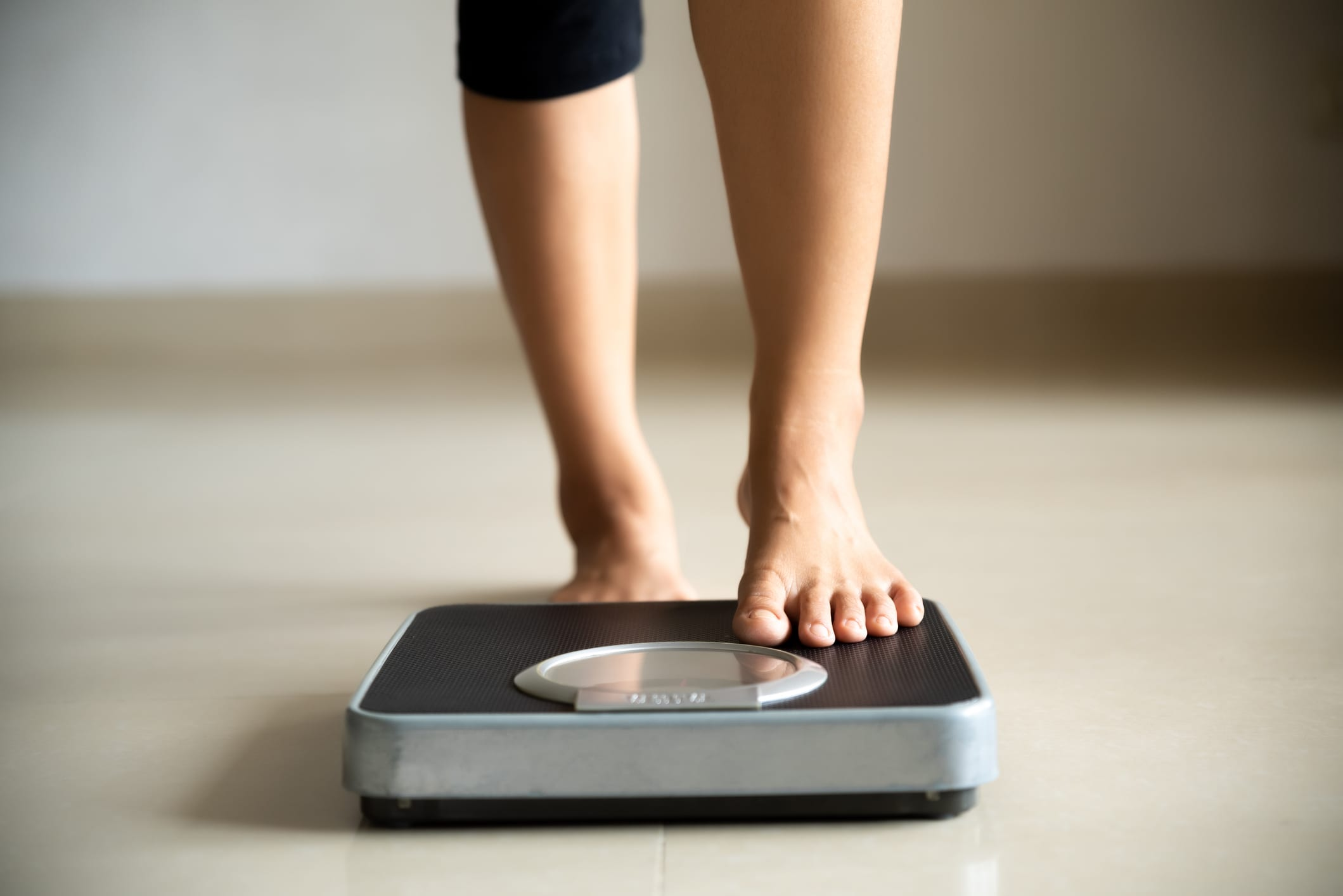 Female leg stepping on weigh scales.