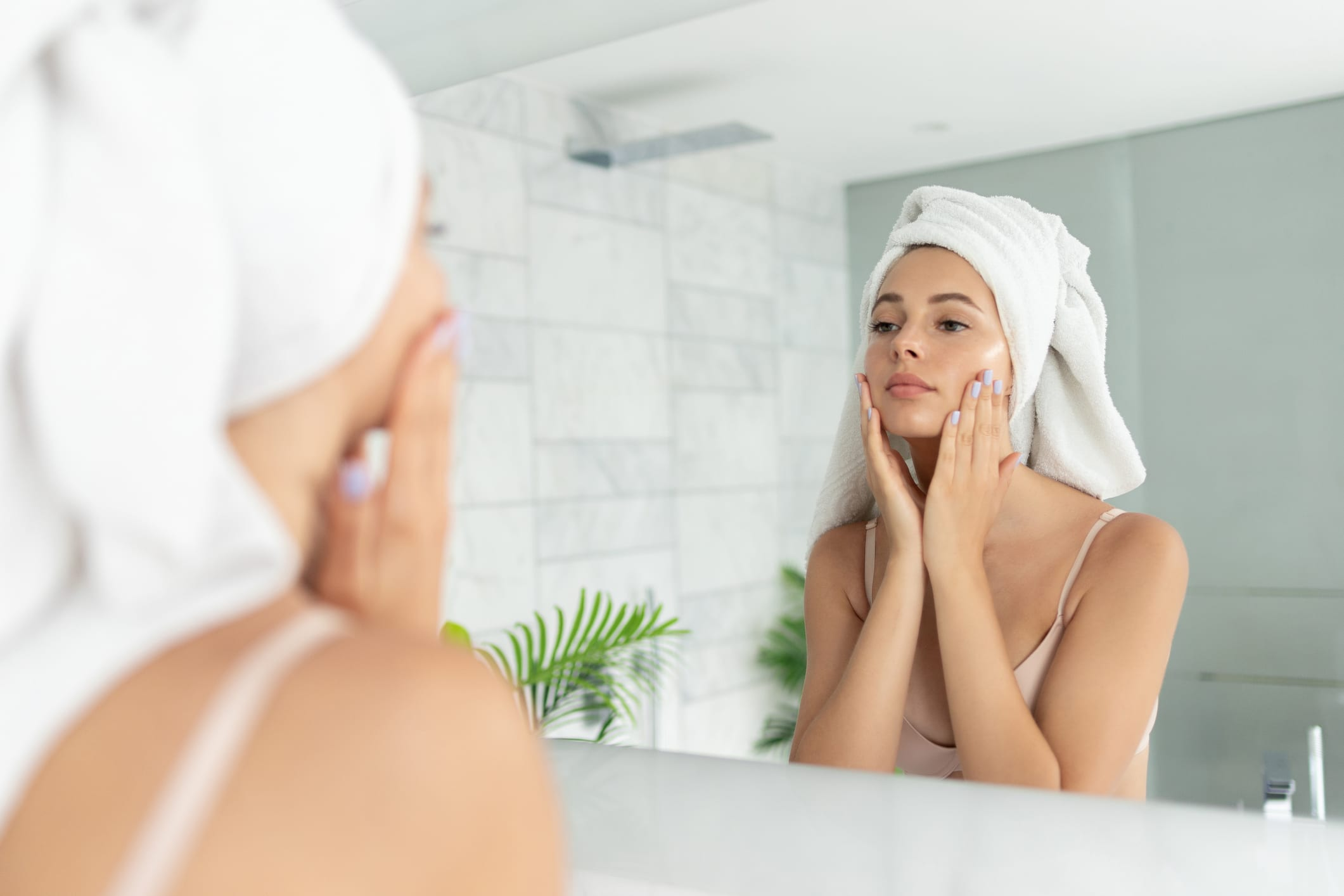 Young beautiful woman using skin face cream lotion