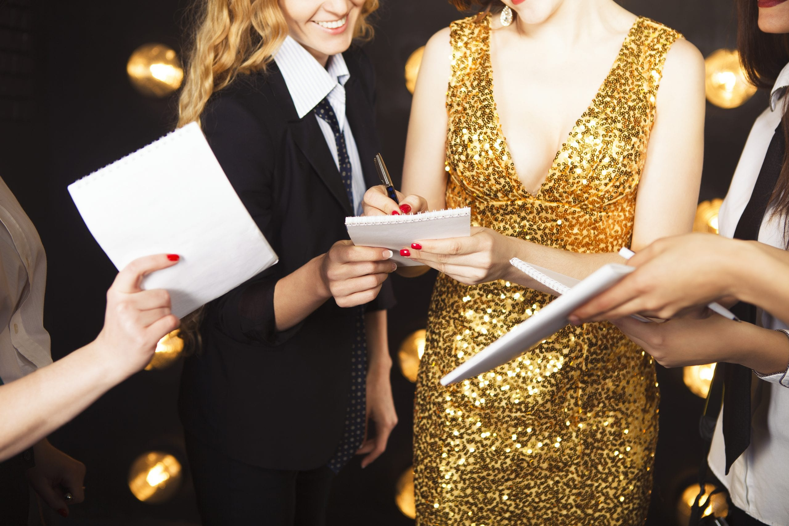 Superstar woman wearing golden shining dress crowded by paparazzi.