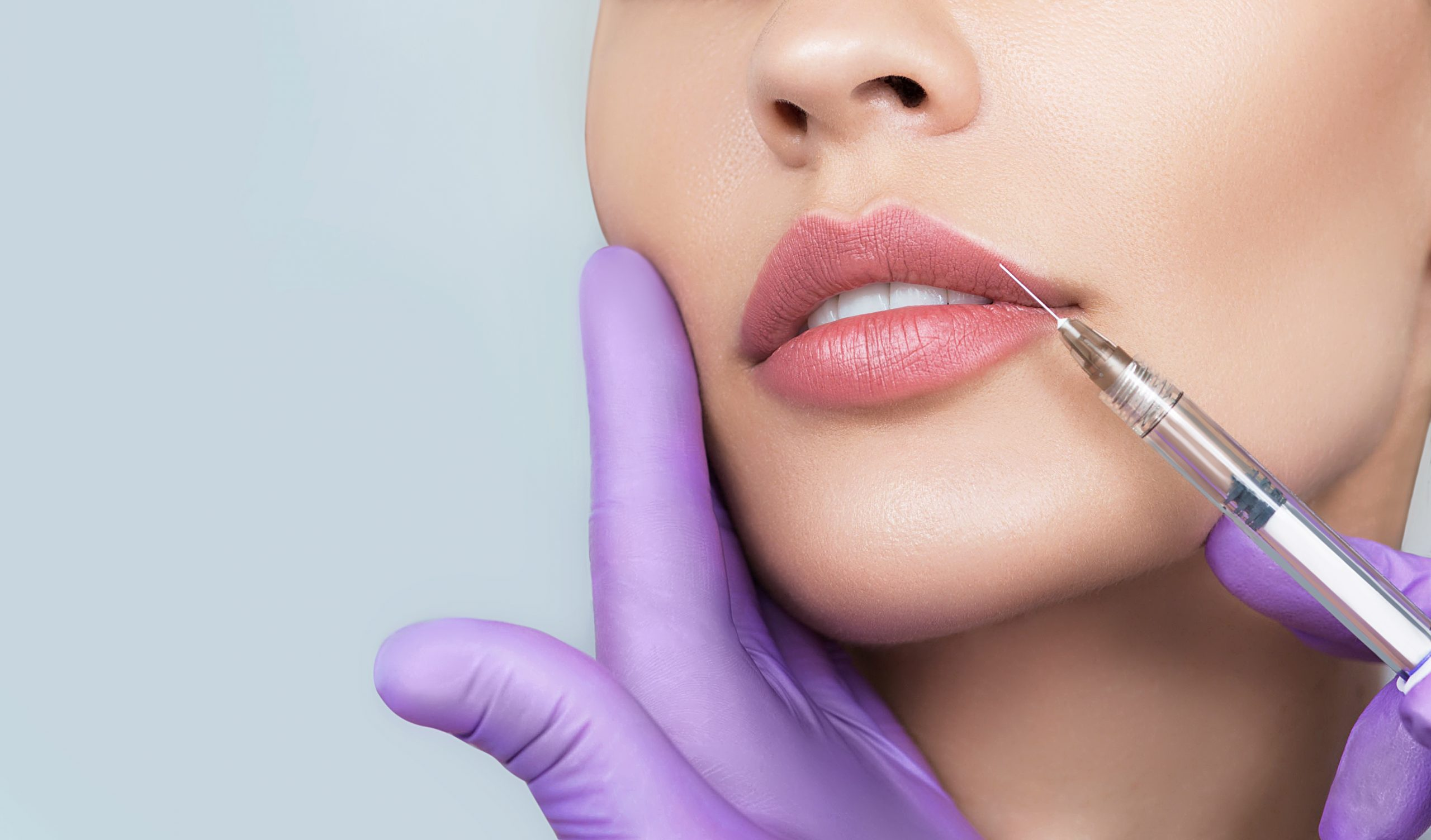 Syringe near woman's mouth, injections for increase lips shape