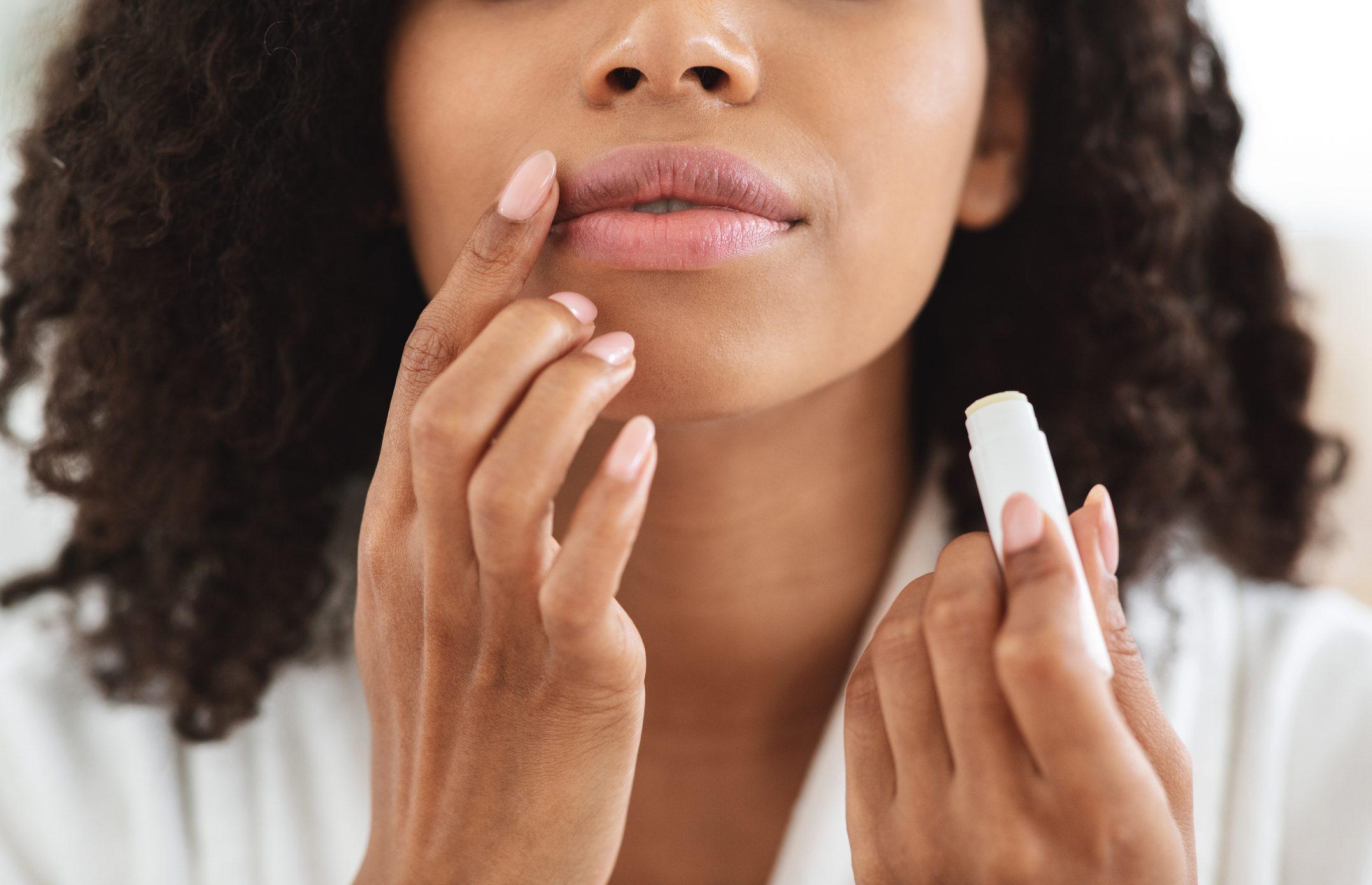 Woman applying moisturising chapstick on lips