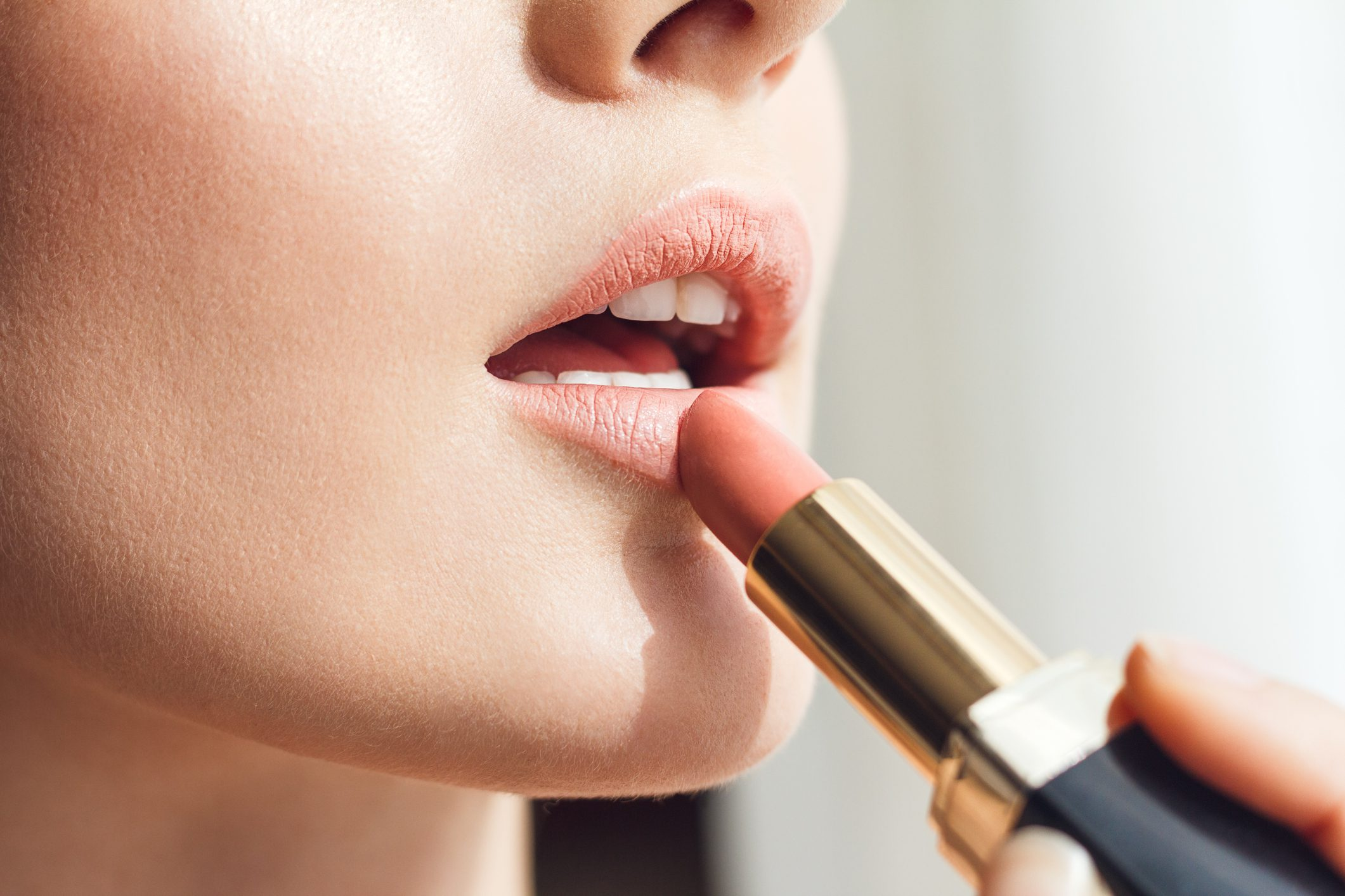 Close up detail of young woman applying lipstick.