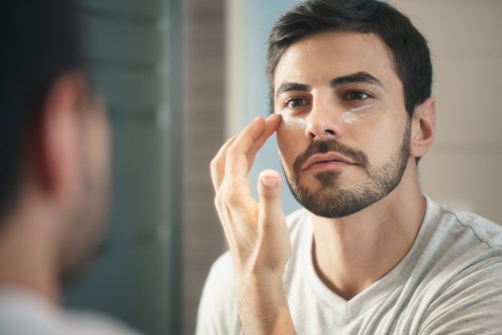 Man using anti-wrinkle products on his skin
